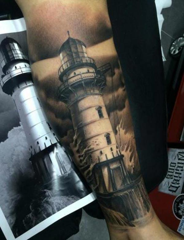 The Lighthouse Tattoo on the side foot of a man make it look attractive