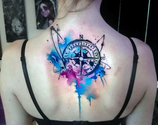 Back tattoo with a blue and black ink design make a girl look elegant