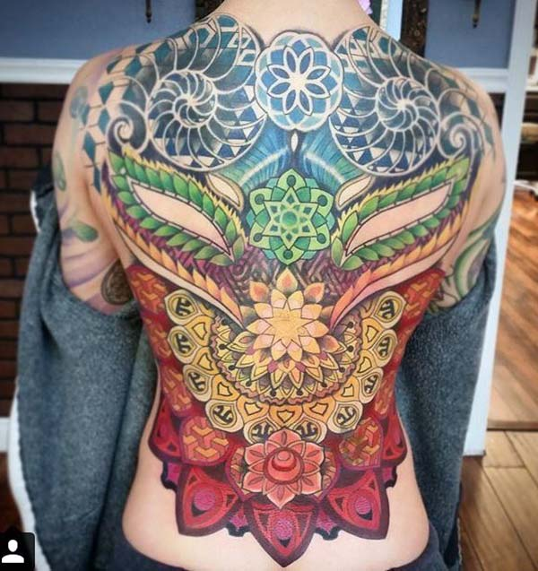 Back Tattoo with a colorful ink design gives the captive look in girls