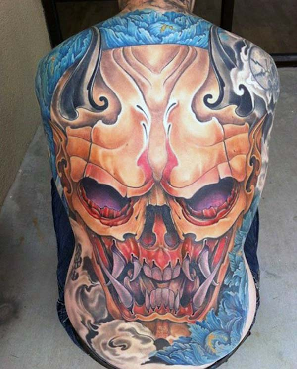 Back Tattoo with a brown and blue ink design making girls to possess an astonishing look