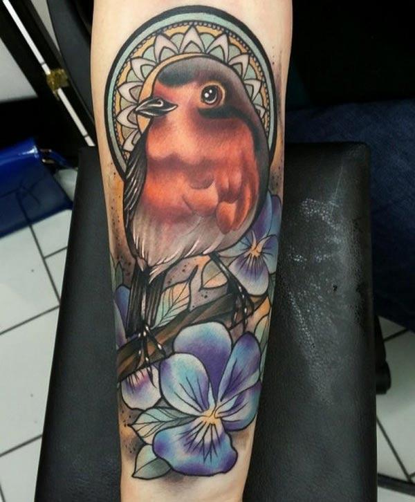Este diseño de tatuaje de pájaro con una tinta colorida hace que la parte inferior del brazo se vea fabulosa