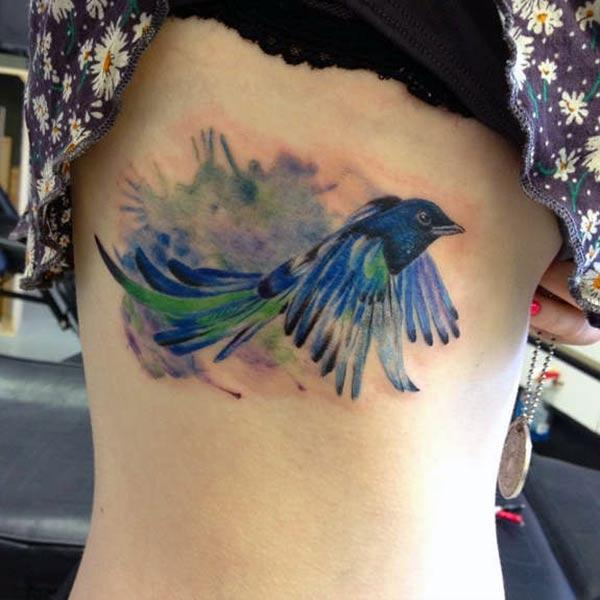Bird tattoo on the side with a blue ink design brings the captivating look