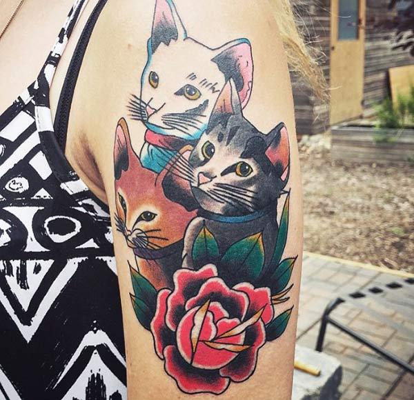 The Cats tattoo on the upper arm has a black ink design that make a lady look gorgeous