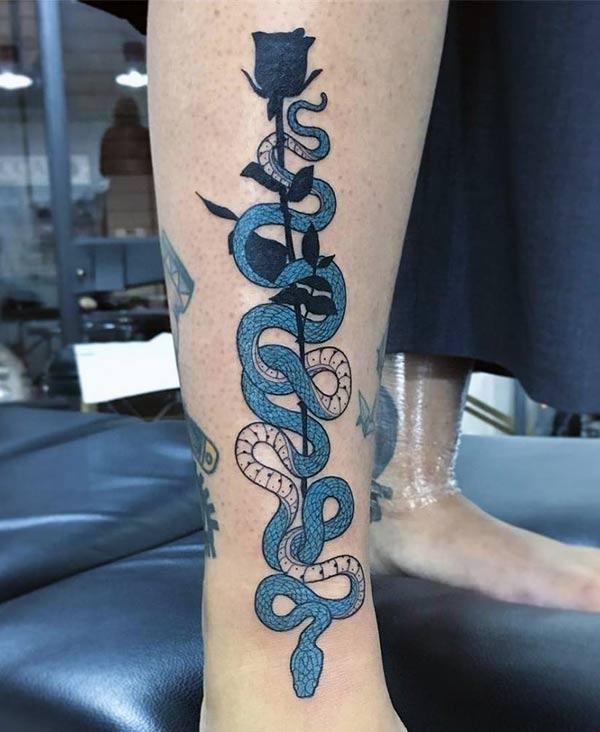 Змія татуювання для жінок на нозі з квітковими та синіми чорнилами змушує їх виглядати стильно.