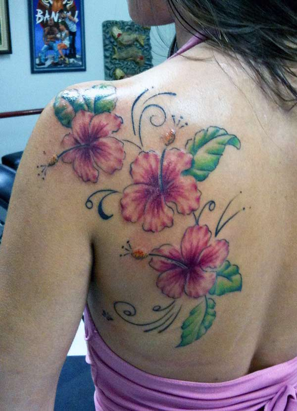 Flower tattoo with pink and green ink on the shoulder makes a girl look admirable.