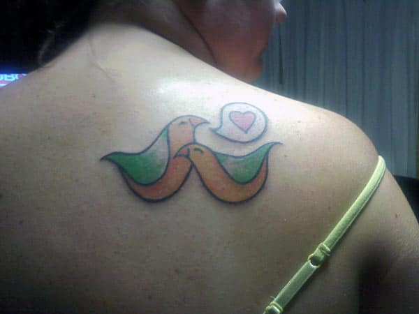 Love tattoo on the shoulder with a green and yellow ink design brings a feminist look