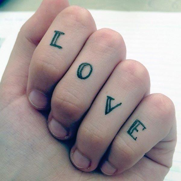 Tattoo love on the fingers make a woman captivating look