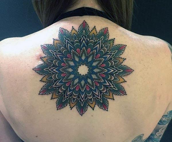 Le dessin à l'encre noire du tatouage Mandala sur le cou arrière, donne aux filles un look splendide