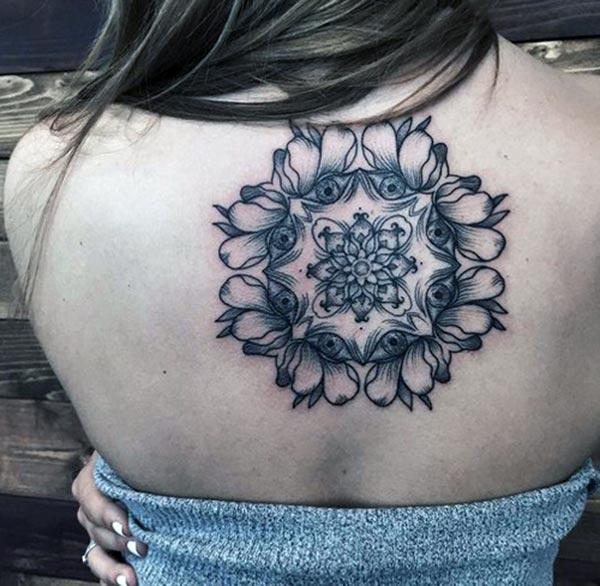 मुलीच्या हातावर असलेली गोंडण गोंदण तिला तिच्या नजरेने चमकदार दिसत आहे