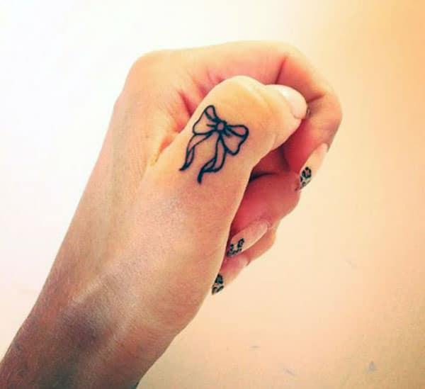Bow tattoo on the finger with black ink mix make it more captivating