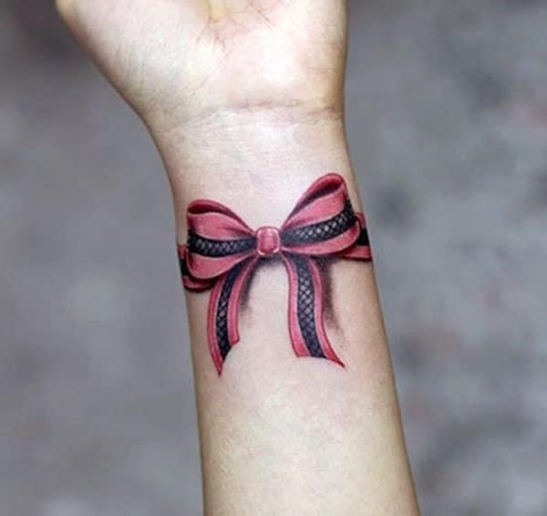 Bow tattoo at the wrist make a girl look comely