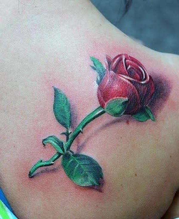 Rose tattoo on the back shoulder with red and green ink design makes a girl appear charming