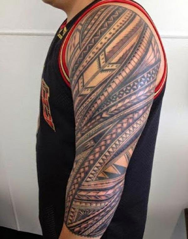 Tribal tattoo on the left arm make a man have an august look