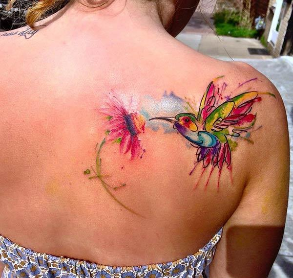 Attractive vibrant hummingbird on flower watercolor tattoo on back shoulder for Females