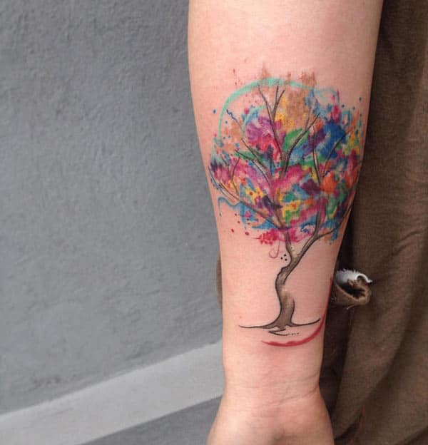 Vibrant colored leaves of tree watercolor tattoo on forearm for stylish women