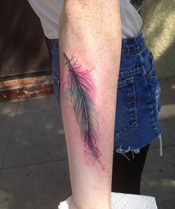 Elegant single feather watercolor tattoo designs on forearm for Women street style look