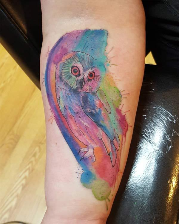 Cool vibrant glaring owl watercolor ink tattoo on forearm for Females