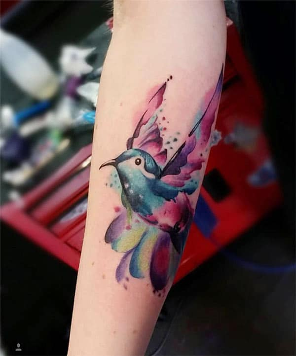 Women's Majestique deep colored flying bird watercolor tattoo on forearm for Chic-ish looks