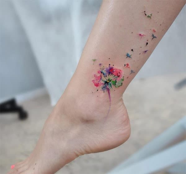 Colorful dandelion flower blown by wind tattoo design on leg for Ladies