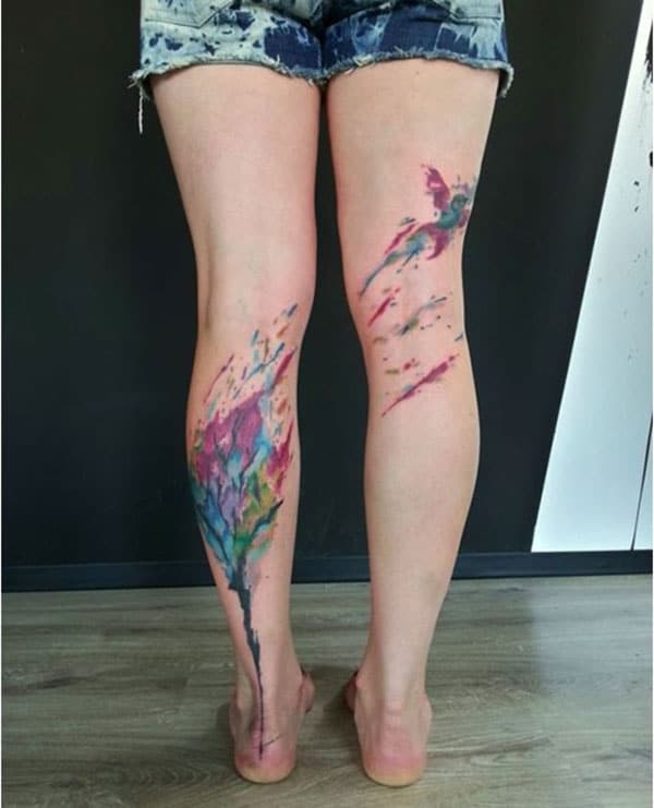 Ink splashy variegated bird flying from colors tattoo design on leg for Females