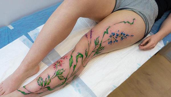 Delightful Flowers with leaves watercolor leg tattoo designs for Women