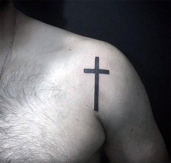 Striking intense black cross tattoo ideas for men on shoulder
