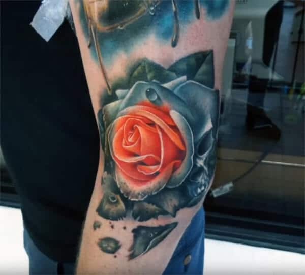 A spectacular red and black rose tattoo designs on elbow for Guys