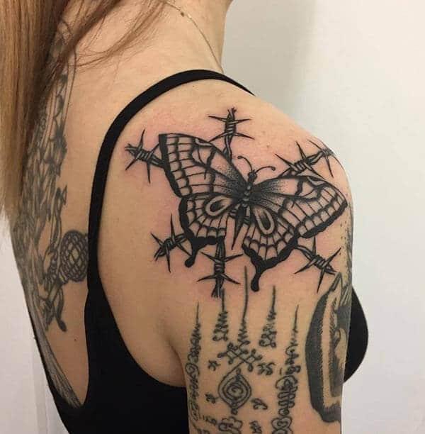 papillon attrayant sur la conception de tatouage d'épines barbelées sur l'épaule