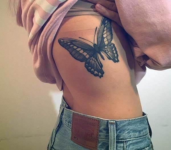 Une conception exquise de tatouage de papillon sur la côte latérale pour des filles