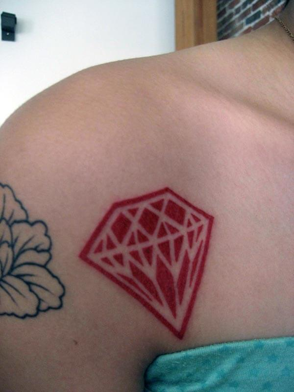 A cute red diamond tattoo on front shoulder for Women