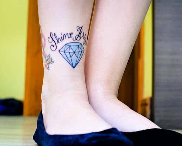 A cute tattoo of blue diamond with Shine Bright wordings on leg for Girls and Women