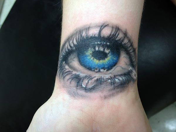 An attractive eye tattoo design on wrist for Women
