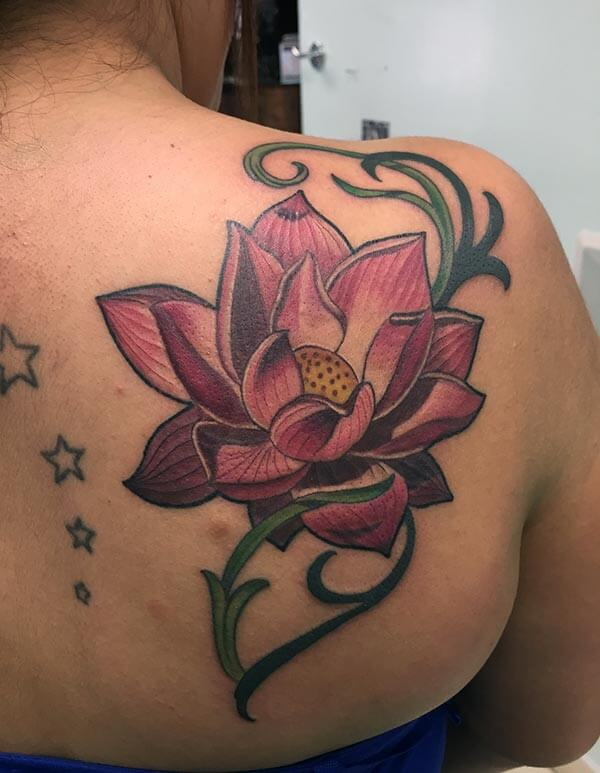 A charming lotus tattoo design on back shoulder for ladies