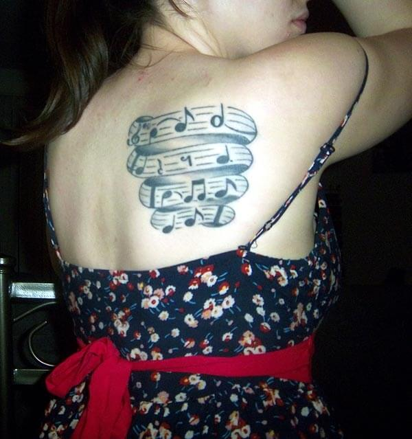 A catchy music tattoo design on back shoulder for women