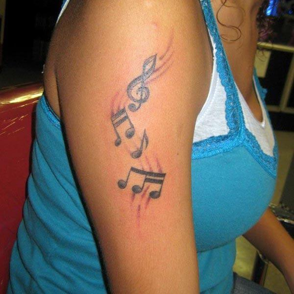 A heartwarming music tattoo design on arm for ladies