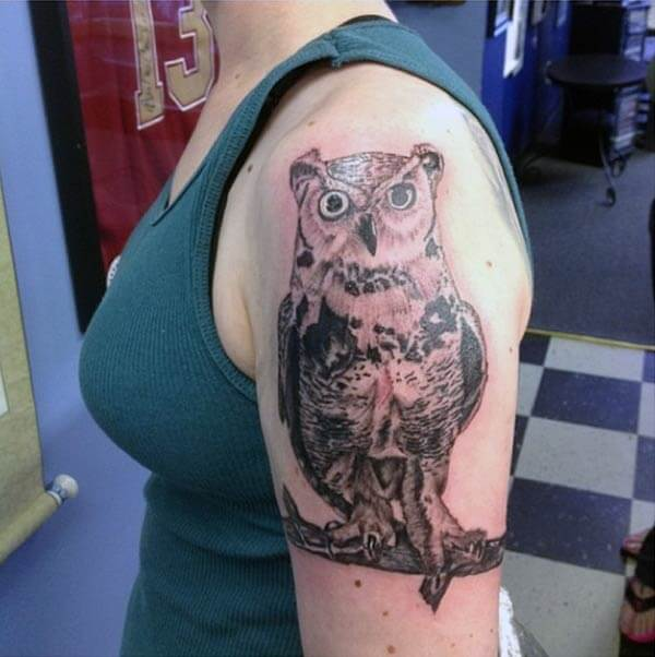 An aesthetic looking owl tattoo design on upper arm for ladies