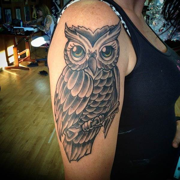 A hypnotizing owl tattoo design on upper arm for women