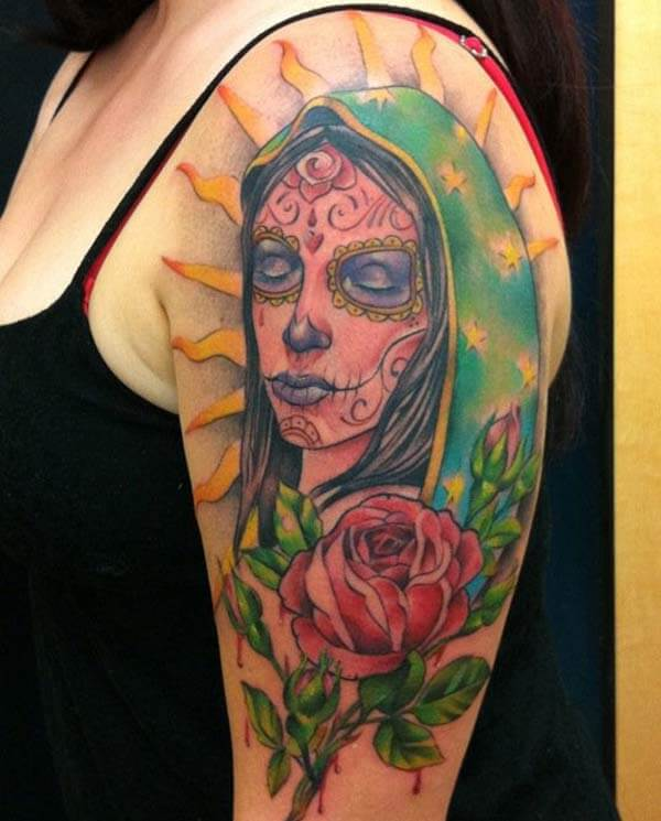 A stunning day of the dead tattoo design on upper arm for women