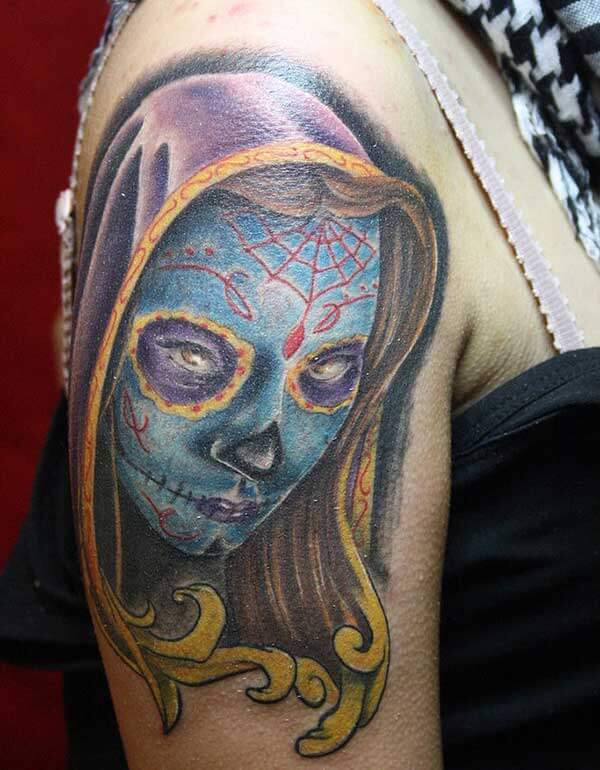 An eye catching day of the dead tattoo design on shoulder for women