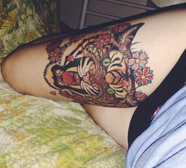 A marvelous tiger tattoo design on thigh for woman