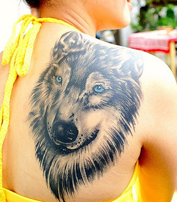 An alluring wolf tattoo design on back shoulder for girls